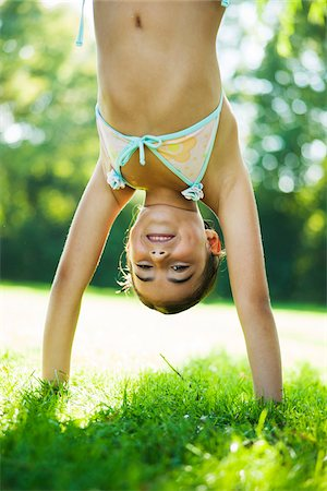 Close-up portrait of young girl doing a handstand on grass, Lampertheim, Hesse, Germany Stock Photo - Premium Royalty-Free, Code: 600-07311413