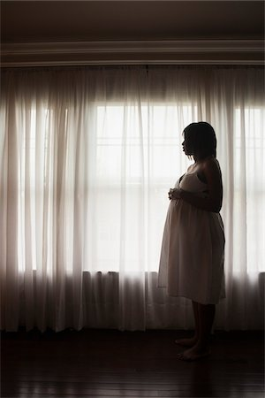 portrait of pregnant woman - Silhouette of Pregnant Woman Looking out Window Stock Photo - Premium Royalty-Free, Code: 600-07311587