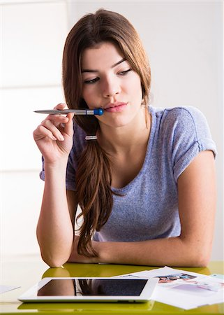 staff - Young woman with pen and tablet computer, thinking and problem solving, studio shot Stock Photo - Premium Royalty-Free, Code: 600-07311598