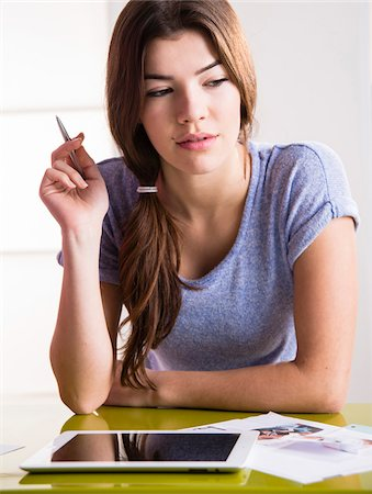 female only - Close-up of young woman with pen and tablet computer, thinking and problem solving, studio shot Stock Photo - Premium Royalty-Free, Code: 600-07311599