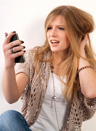 Young, blond, long-haired woman staring at cellphone with disbelief, studio shot on white background Stock Photo - Premium Royalty-Free, Code: 600-07348155