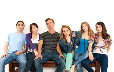 Portrait of six young people sitting together on a bench, studio shot on white background Stock Photo - Premium Royalty-Free, Code: 600-07348159