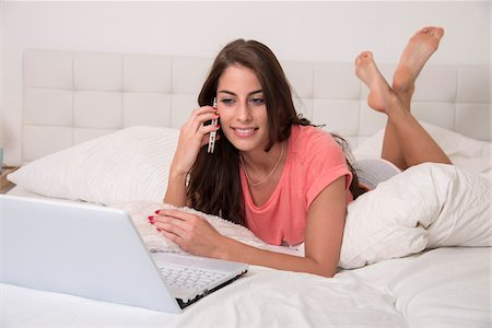 Young Woman using Cellphone and Laptop in Bed Stock Photo - Premium Royalty-Free, Code: 600-07355304