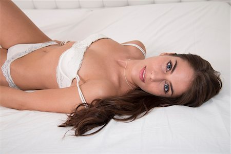 sexy - Portrait of Young Woman Laying on Bed Looking at Camera Stock Photo - Premium Royalty-Free, Code: 600-07355307