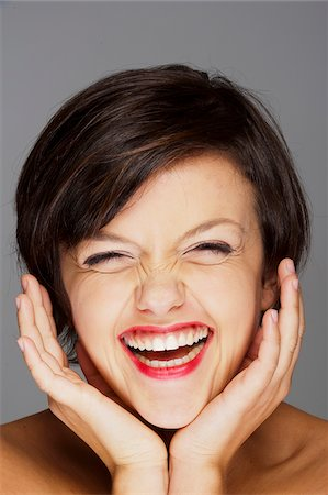 Head and Shoulders Portrait of Mid-Adult Woman Laughing with Grey Background Stock Photo - Premium Royalty-Free, Code: 600-07355317