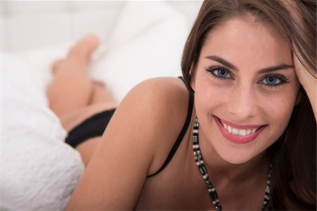 sexy - Portrait of Young Woman Laying on Bed Looking at Camera Stock Photo - Premium Royalty-Free, Code: 600-07355310