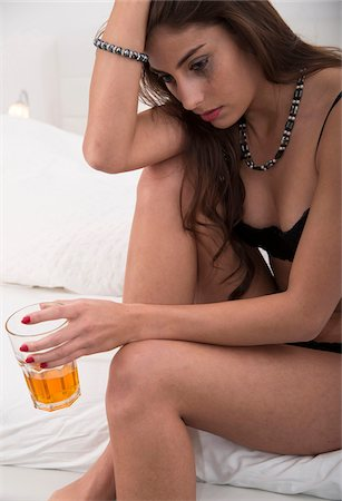 Young Woman with Drink and Smudged Make-up in Bedroom Stock Photo - Premium Royalty-Free, Code: 600-07351342