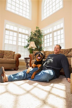 fat man full body - Portrait of Mature Man with his Pet Rottweiler in Living Room Stock Photo - Premium Royalty-Free, Code: 600-07368545