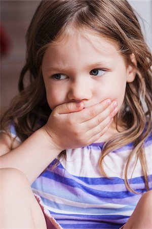 Close-up of Girl with Hand covering her Mouth Stock Photo - Premium Royalty-Free, Code: 600-07363885