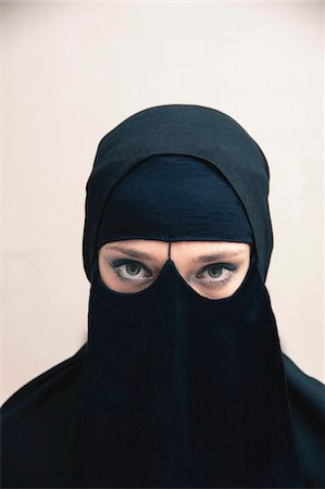 restrained - Close-up portrait of young woman wearing black, muslim hijab and muslim dress, eyes looking at camera showing eye makeup, studio shot on white background Stock Photo - Premium Royalty-Free, Code: 600-07434925