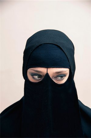 restrained - Close-up portrait of young woman wearing black, muslim hijab and muslim dress, eyes looking to the side showing eye makeup, studio shot on white background Stock Photo - Premium Royalty-Free, Code: 600-07434926