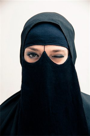 restrained - Close-up portrait of young woman wearing black, muslim hijab and muslim dress, winking and looking at camera, eyes showing eye makeup, studio shot on white background Stock Photo - Premium Royalty-Free, Code: 600-07434927