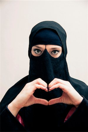 displaying - Close-up portrait of young woman wearing black, muslim hijab and muslim dress, making heart shape with hands, looking at camera, eyes showing eye makeup, studio shot on white background Stock Photo - Premium Royalty-Free, Code: 600-07434928