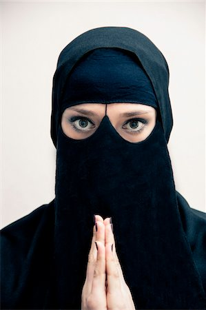 restrained - Close-up portrait of young woman wearing black, muslim hijab and muslim dress, with hands praying, looking at camera, eyes showing eye makeup, studio shot on white background Stock Photo - Premium Royalty-Free, Code: 600-07434929
