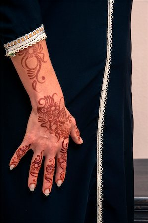 design (motif, artistic composition or finished product) - Woman standing indoors, with close-up of arms and hand painted with henna in arabic style, wearing a typical black, arabic, muslim dress, studio shot Stock Photo - Premium Royalty-Free, Code: 600-07434934