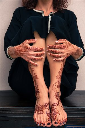 Low section of woman sitting indoors, showing legs, feet and hands painted with henna in arabic style, wearing a typical black, arabic, muslim dress, studio shot Stock Photo - Premium Royalty-Free, Code: 600-07434936