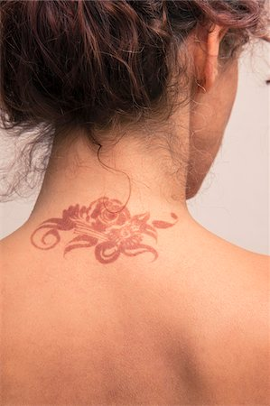 Close-up of woman's back and neck showing detail of henna painted tattoo in arabic style, studio shot on white background Stock Photo - Premium Royalty-Free, Code: 600-07434937