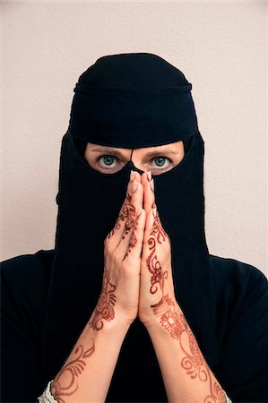 Close-up portrait of woman wearing black muslim hijab and muslim dress looking at camera, with hands praying and showing arms and hands painted with henna in arabic style, studio shot on whtie background Stock Photo - Premium Royalty-Free, Code: 600-07434938
