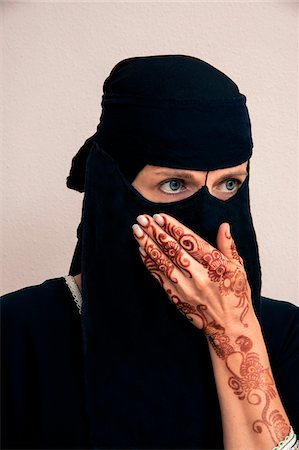 female silhouette head and hand - Close-up portrait of woman wearing black muslim hijab and muslim dress, looking to the side with hand covering mouth and showing arms and hands painted with henna in arabic style, studio shot on whtie background Stock Photo - Premium Royalty-Free, Code: 600-07434939