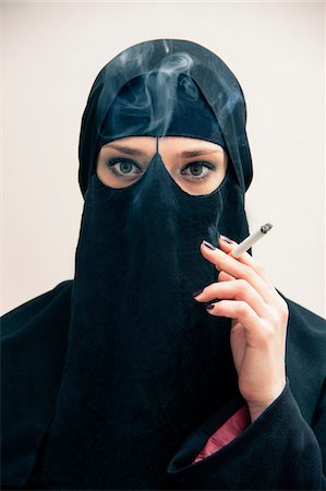 Close-up portrait of young woman wearing black, muslim hijab and muslim dress, holding cigarette and smoking, looking at camera, eyes showing eye makeup, studio shot on white background Stock Photo - Premium Royalty-Free, Code: 600-07434930