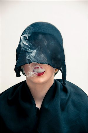 Close-up portrait of young woman wearing black, muslim dress and black, hijab covering part of head, while blowing smoke from red lips, studio shot on white background Stock Photo - Premium Royalty-Free, Code: 600-07434931