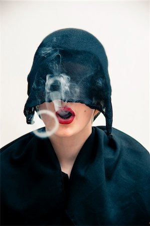 Close-up portrait of young woman wearing black, muslim dress and black, hijab covering part of head, while blowing smoke rings from red lips, studio shot on white background Stock Photo - Premium Royalty-Free, Code: 600-07434932