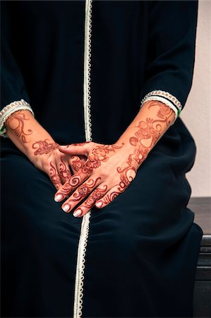 restrained - Woman sitting indoors with close-up of arms and hands painted with henna in arabic style, wearing a typical black, arabic, muslim dress, studio shot Stock Photo - Premium Royalty-Free, Code: 600-07434933