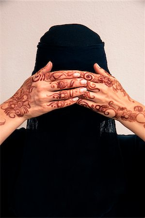 female silhouette head and hand - Close-up portrait of woman wearing black muslim hijab and muslim dress, hands covering eyes and showing hands painted with henna in arabic style, studio shot on whtie background Stock Photo - Premium Royalty-Free, Code: 600-07434940