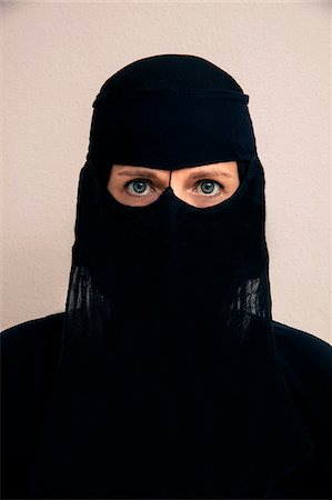 restrained - Close-up portrait of woman wearing black muslim hijab and muslim dress, looking at camera, studio shot on white background Stock Photo - Premium Royalty-Free, Code: 600-07434941