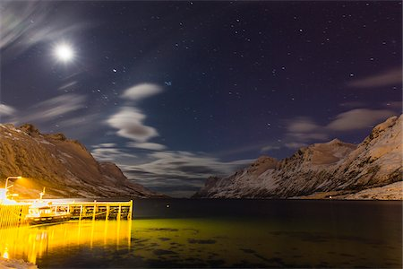 star sky night - Boat and dock lit up at night with moon illuminating snow covered mountains at a fjord in the Arctic, Norway Stock Photo - Premium Royalty-Free, Code: 600-07453770