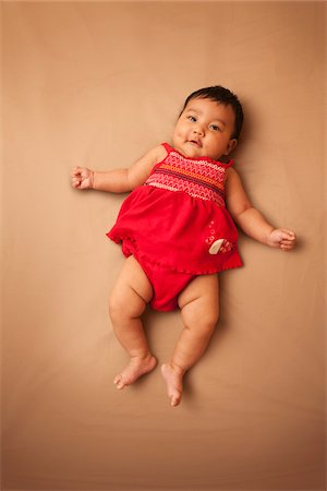 Portrait of Asian baby lying on back, wearing red dress, looking at camera and smiling, studio shot on brown background Stock Photo - Premium Royalty-Free, Code: 600-07453952