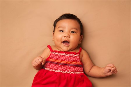 Close-up portrait of Asian baby lying on back, wearing red dress, looking at camera and smiling, studio shot on brown background Stock Photo - Premium Royalty-Free, Code: 600-07453953