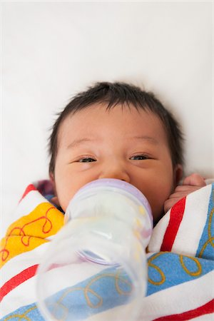 Close-up of two week old, newborn Asian baby girl wrapped in colorful swaddling blanket, drinking from baby bottle, studio shot Stock Photo - Premium Royalty-Free, Code: 600-07453967