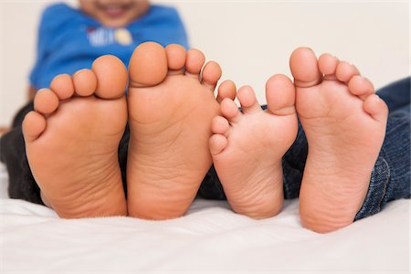 Brother and sister lying in bed together, close-up of the soles of their feet, studio shot Stock Photo - Premium Royalty-Free, Code: 600-07453968