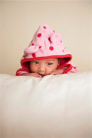 southeast asian ethnicity - Portrait of two week old, newborn Asian baby girl in pink polka dot hooded jacket, studio shot on white background Stock Photo - Premium Royalty-Free, Code: 600-07453960