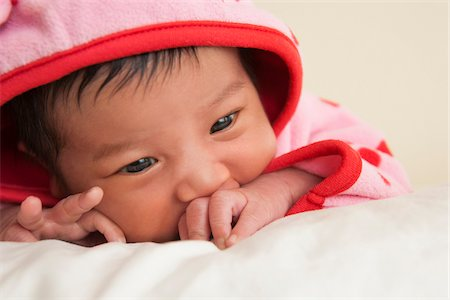 Close-up portrait of two week old Asian baby girl in pink polka dot hooded jacket, studio shot Stock Photo - Premium Royalty-Free, Code: 600-07453962