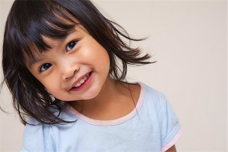 Close-up portrait of Asian toddler girl, looking at camera and smiling, studio shot on white background Stock Photo - Premium Royalty-Free, Code: 600-07453970