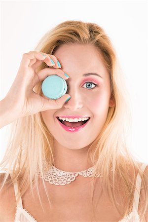 pretty - Close-up portrait of young woman holding blue macaron up to her eye, looking at camera and smiling, studio shot on white background Stock Photo - Premium Royalty-Free, Code: 600-07487658