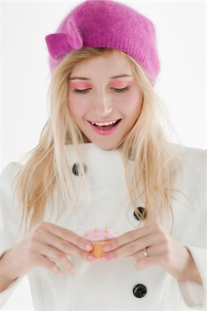 Close-up portrait of young woman wearing pink hat and holding cupcake, studio shot on white background Stock Photo - Premium Royalty-Free, Code: 600-07487664
