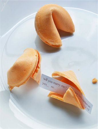 Close-up of fortune cookies on white plate, showing text for marriage proposal, studio shot Stock Photo - Premium Royalty-Free, Code: 600-07529005