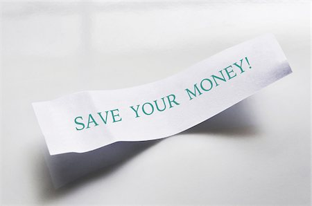savings - Close-up of message from fortune cookie on white plate, showing text for saving money, studio shot on white background Stock Photo - Premium Royalty-Free, Code: 600-07529009