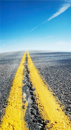 Close-up view of yellow center lines on deserted highway with blue sky, Canada Stock Photo - Premium Royalty-Free, Code: 600-07529012