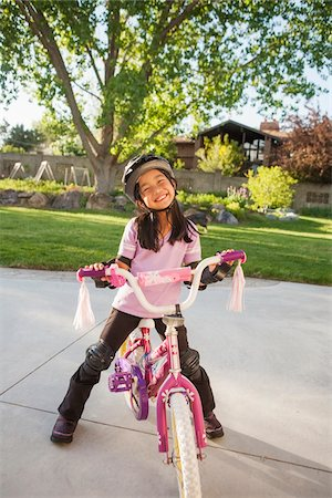 dark hair - Portrait of Girl Riding Bike with Safety Gear, Utah, USA Stock Photo - Premium Royalty-Free, Code: 600-07529201
