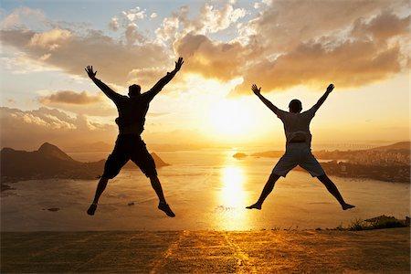Teenagers doing Star Jumps at Sunset overlooking Rio de Janeiro, Brazil Stock Photo - Premium Royalty-Free, Code: 600-07541413