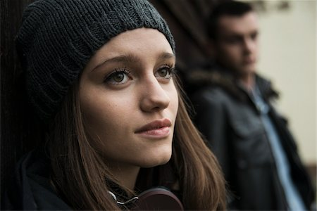Close-up portrait of teenage girl outdoors, wearing hat and headphones around neck, with young man in background, Germany Stock Photo - Premium Royalty-Free, Code: 600-07567384