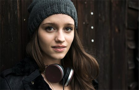 Close-up portrait of teenage girl outdoors, wearing hat and headphones around neck, looking at camera and smiling, Germany Stock Photo - Premium Royalty-Free, Code: 600-07567385