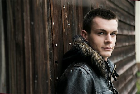 Close-up of young man wearing jacket outdoors, looking at camera, Germany Stock Photo - Premium Royalty-Free, Code: 600-07567391
