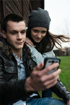 Close-up of young man and teenage girl outdoors, looking at cell phone, Germany Stock Photo - Premium Royalty-Free, Code: 600-07567392