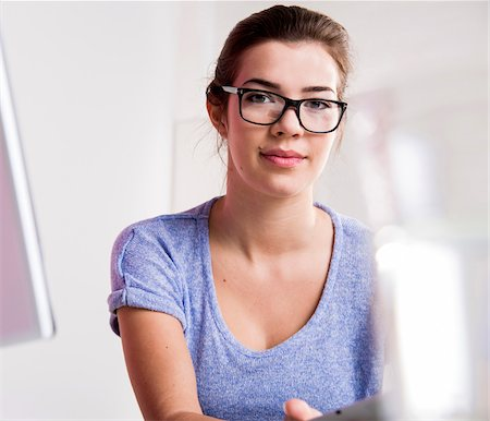 female only - Portrait of young woman in office, wearing horn-rimmed eyeglasses and looking at camera, Germany Stock Photo - Premium Royalty-Free, Code: 600-07584754