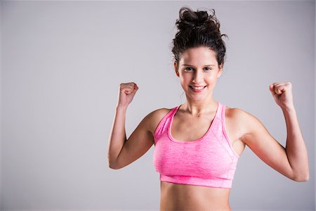 Close-up portrait of teenage girl exercising, smiling and looking at camera, studio shot on grey background Stock Photo - Premium Royalty-Free, Code: 600-07584750